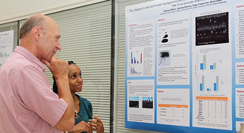 student and faculty member reading scientific poster