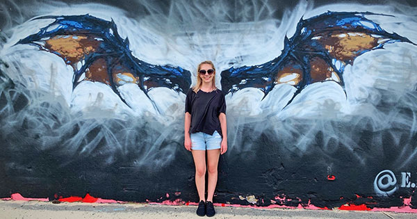 [Sara Colin poses in front of a mural of a bat]