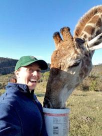 Rachel Stuart feeds a giraffe]