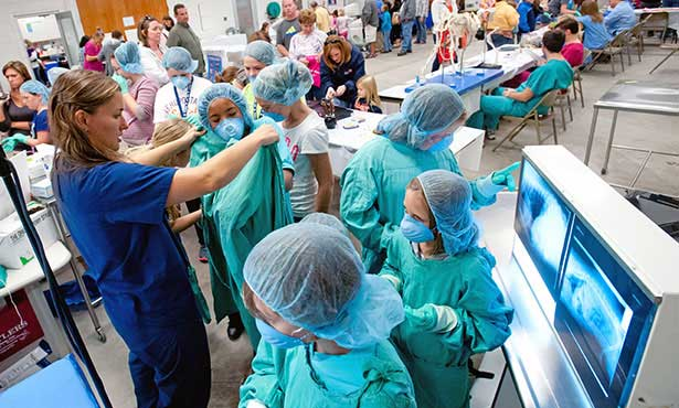 [visitors gown up for mock surgery at Open House]