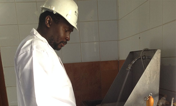 Dr. Takalani Netshituni demonstrates the use of a hands free wash station at a slaughterhouse.