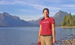 Dr. Casey Cadile poses in front of a mountain while on an adventure with her dog Summer.