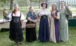 Rose Ann Meccoli poses with veterinary students at a medieval fair with the resident birds of prey
