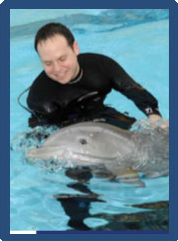 Ben Nevitt smiles at the dolphin he is in the water with.