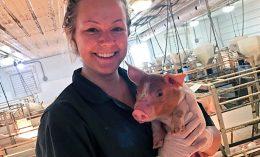 [Dr. Brandi Burton holds a piglet]