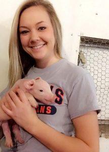 [Brandi Burton with a piglet]