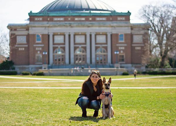 [Anita Kalonaros and her dog in front of Foellinger Auditorium]