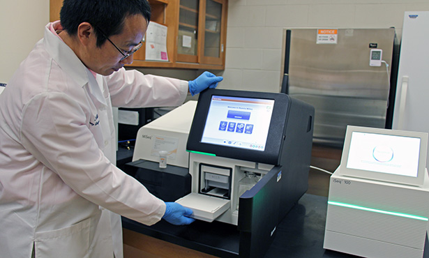 [Dr. Leyi Wang with whole-genome sequencers]