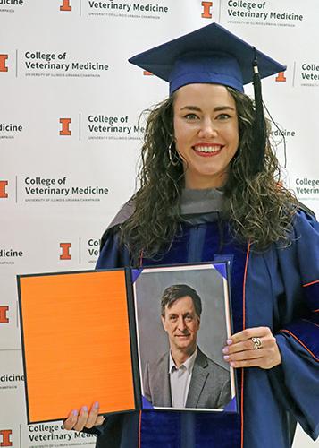 [Dr. Sophia Ochs holds photo of Dr. Ian Sprandel]