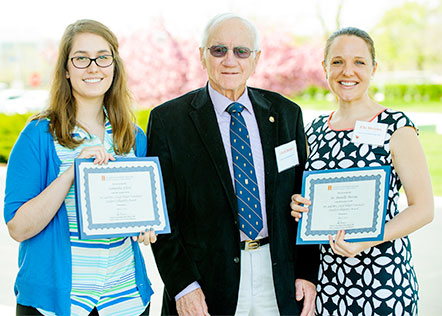 [Dr. Helper between student and faculty award winners]